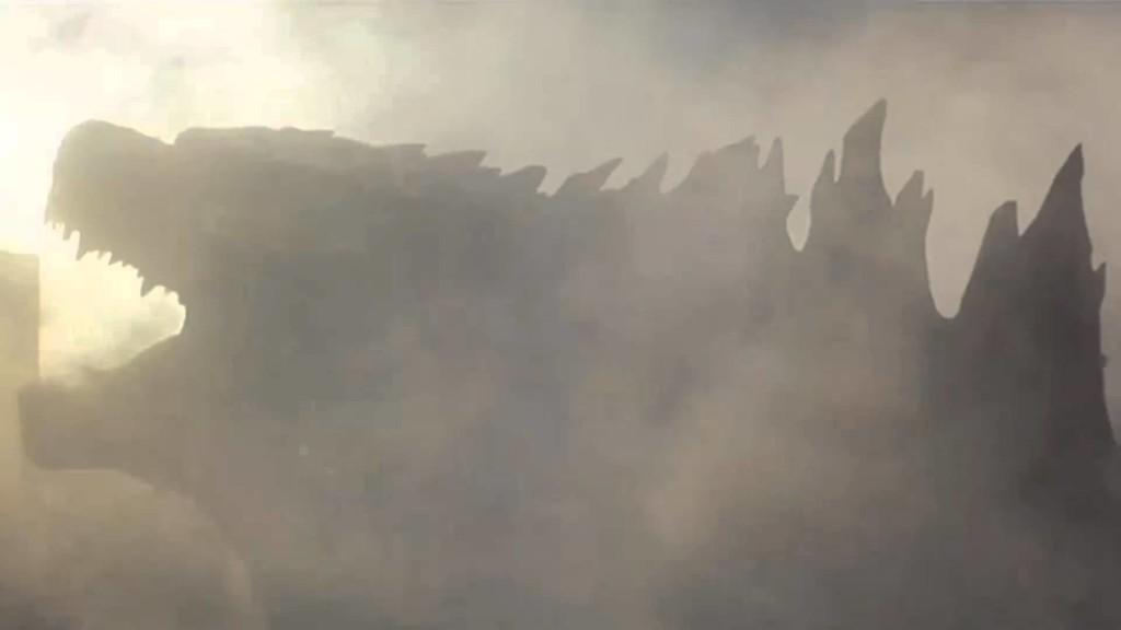 La sagoma di Godzilla tra il fumo e la polvere delle macerie che ha causato